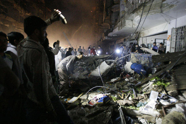 Pakistanis check the site of a bomb blast in Karachi on Sunday. Officials say dozens of people were killed in a neighborhood dominated by Shiite Muslims in Pakistan's largest city.