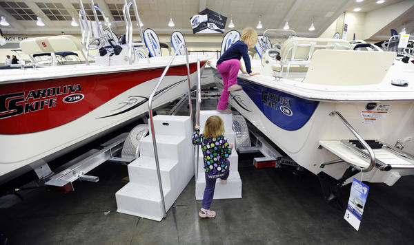 Lucy Trumbauer, 3, of Chestertown, follows her sister Alida, 5, onto a Carolina Skiff during the Progressive Baltimore Boat Show, Maryland's longest-running boat show.