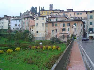 Barga is clustered on a hilltop in a mountainous region of Northern Tuscany. The green hillside is part of Kennedy Brothers Park.