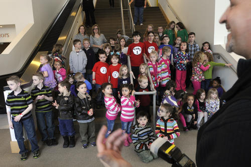 Brian Ambrse, right, of Glastonbury, the Science Center's official photographer, assembles the children on a stairwell inside the center for an official portrait.