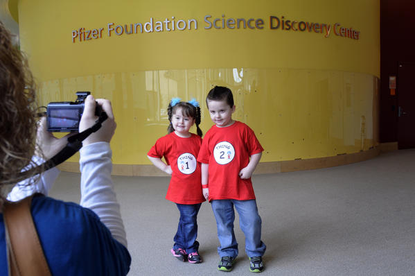 Dorothy Zyla takes a photo of her three-and-one-half-year old twins, Leah, and Jaxson, in the lobby of the center. Zyla joined other twins in a group photo before taking the children into the science center.