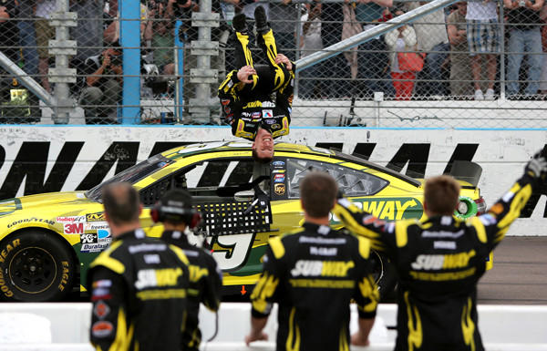 NASCAR driver Carl Edwards performs his trademark backflip after winning the Sprint Cup Series race at Phoenix International Raceway on Sunday.