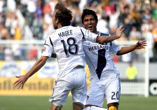 Galaxy's Mike Magee celebrates one of his three goals with teammate A.J. DeLaGarza.