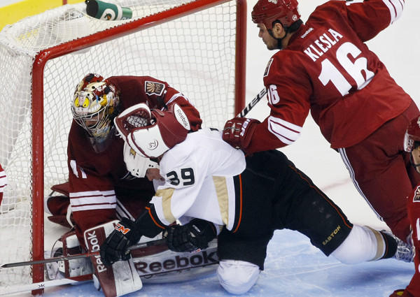 Coyotes goalie Mike Smith and defenseman Rostislav Klela take down Ducks left wing Matt Beleskey (39) in the third period Saturday.