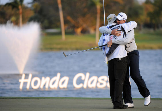Michael Thompson celebrates winning the Honda Classic with his caddie Matt Bednarski.