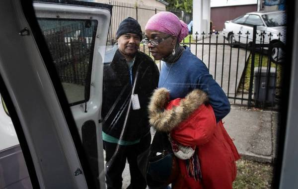 Driver Calvin Woodard opens his van door for Carmel Neal, who has an afternoon appointment at T.H.E. Clinic in South Los Angeles. Every weekday, Woodard, 59, ferries dozens of patients to and from the clinic.