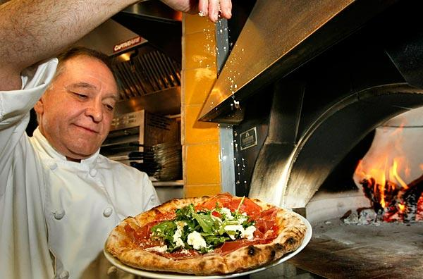 Il Dolce owner Roberto Bigne finishes off a prosciutto and arugula pizza from the oven.