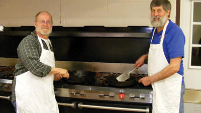 Steve Hoover (left) and Dick Shunk are cooking up the sausage at the Salisbury Municipal Building for a Maple Sugarin' Dinner. The dinners are served by the Salisbury Lions Club from 8 a.m. to 4 p.m. each day, March 16-17 and March 23-24. This is the organization's largest fundraiser.