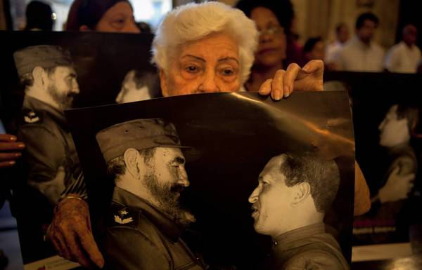 People at a Mass in Havana in January hold posters showing Cuba's Fidel Castro, left, and Venezuelan President Hugo Chavez. The parishioners were praying for the recovery of Chavez, who has cancer.