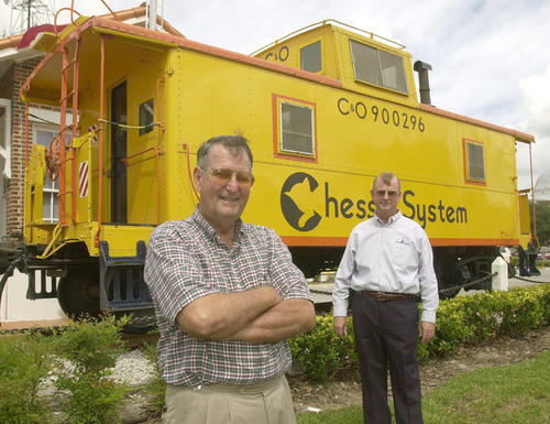 Winter Garden Heritage Museum president Larry Grimes and board member Phil Cross (right) in front of the bright yellow caboose that sits in front of the museum in downtown Winter Garden.