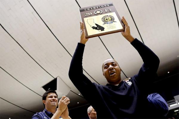 St. John Bosco head coach Derrick Taylor raises the championship plaque after winning the CIF Division 3A High School Basketball final.