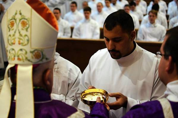 Khalil Hattar, of Tinley Park, kneels before clergy Sunday at Pontifical North American College in Rome during his institution as a Roman Catholic acolyte, the third step toward becoming a priest.