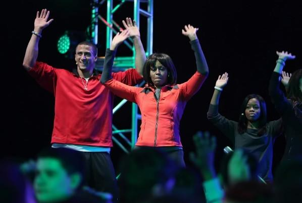 "Colin Kaepernick (left) and Gabby Douglas (right) dance with First Lady Michelle Obama (center) at the launch of the ""Let's Move! Active Schools"" initiative at McCormick Pace, Feb. 27, 2013"