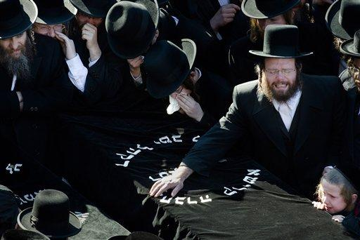 Members of the Satmar Orthodox Jewish community grieve over the coffins at the funeral for two expectant parents who were killed in a car accident Sunday in Brooklyn, N.Y. A driver struck their car early Sunday morning, killing both parents. Their baby, who was born prematurely, died Monday.
