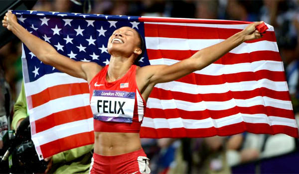 "USA's Allyson Felix carries the American flag after winning the 200 meters at the 2012 London Olympics. <a href=""http://www.lasports.org"">www.lasports.org</a>."