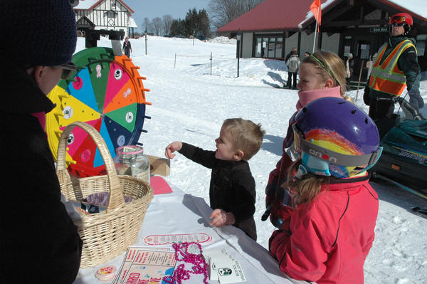 "Alison Hubbard (from left), annual giving manager at McLaren Northern Michigan, helps Bodie Evenhouse, 5, of Holland, spin the wheel at a tent set up for ""Boarding for Breast Cancer."" With him are Josie Evenhouse, 10, and Annie Molenhouse, 5, both also of Holland. The event aimed to raise money for breast cancer awareness, research and medical needs for the nation-wide nonprofit ""Boarding for Breast Cancer"" and for McLaren Northern Michigan's Kathleen Jontz Breast Health Fund. Hubbard and one of the organizer of events, Nicole Belmont, activities director for Boyne Highlands, say the skiing and snowboarding aspect of the organization helps draw in young adults and children."