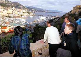 Asian tourists watch the Monaco harbor.