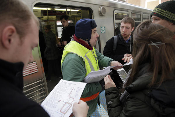 Commuters gather around a CTA employee for information on trains into the Loop.