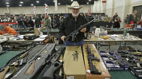 Ken Haiterman, of Pioneer Market, holds a CMMG 5.56mm AR-15 during the 2013 Rocky Mountain Gun Show in Sandy, Utah.