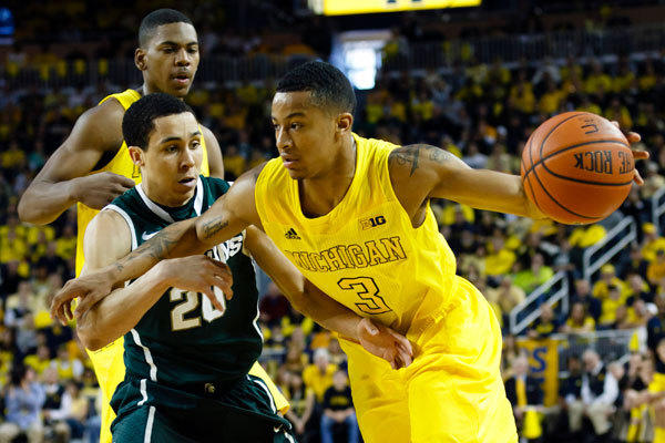 Michigan Wolverines guard Trey Burke (3) moves the ball on Michigan State Spartans guard Travis Trice (20) in the first half at Crisler Center.