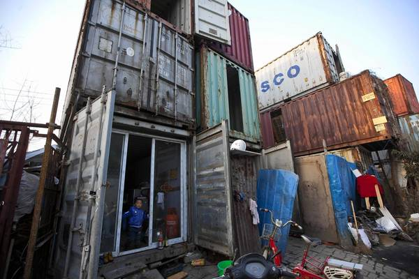 A child stands at the door of a shipping container serving as his accommodation, in Shanghai. The containers, which house different families, were set up by the landlord, who charges a rent of 500 yuan ($ 80) per month for each container.