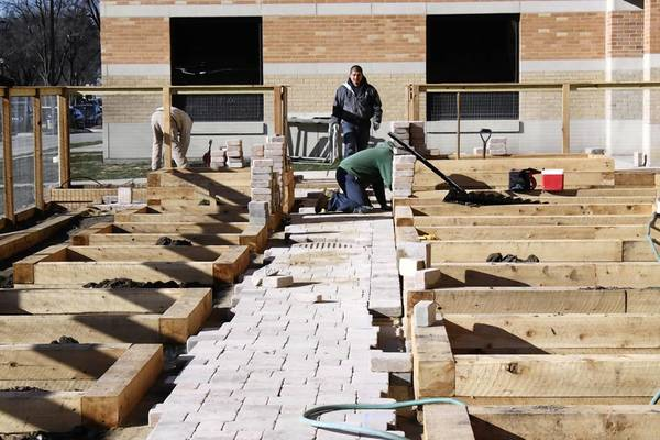 Workers construct a garden for the Northbrook Junior High School in November. The outdoor classroom is expected to open in April.