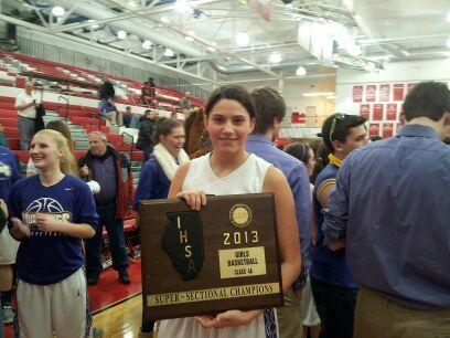 Ashely Montanez of Rolling Meadows High School holds her team's supersectional plaque after its win against Evanston.