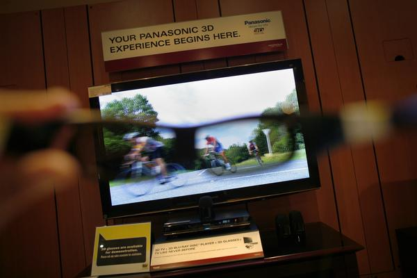 3-D glasses are held up to a 50-inch plasma 3-D television set.
