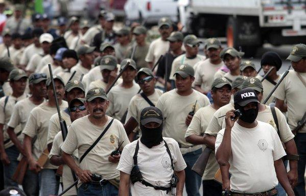 Community police members take part in the March for Justice and Dignity in the town of Ayutla de los Libres in Guerrero state on Saturday. Hundreds of armed civilians have begun providing security for communities in the state, creating a vigilante force.