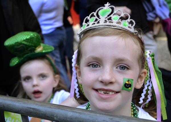 Meghan Donahue, 4, of Baltimore, in back at left, and Bridget May, 5, of Rodgers Forge, at right, watch the St. Patrick's Day Parade on North Charles Street.