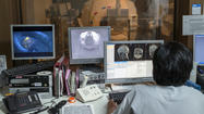 A doctor controls the progress of an MRI of a child who first underwent a fake preparatory CT scan.