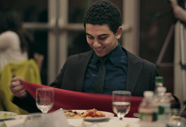 Sophomore Emad William, 21, who is studying computer science at MIT, learns the proper way to place his napkin in his lap.