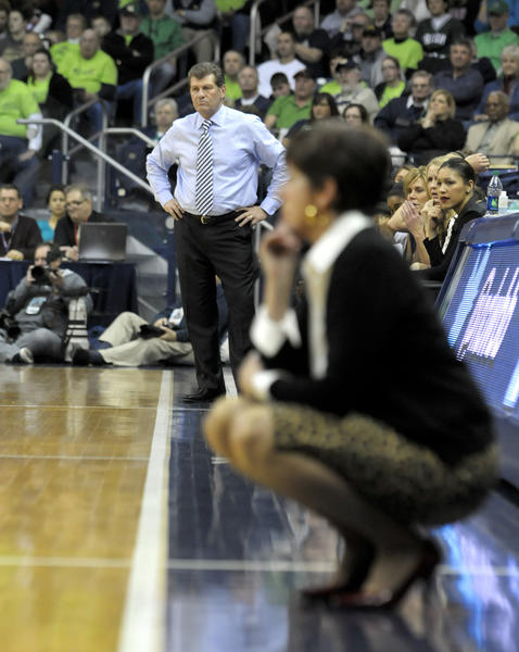 UConn coach Geno Auriemma and  Notre Dame coach Muffet McGraw watch the action as their teams meet in the regular season finale. Notre Dame won, 96-87.