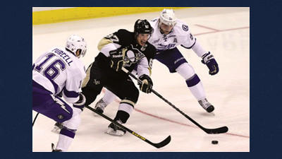 Pittsburgh Penguins center Sidney Crosby (87) gets a pass off between Tampa Bay Lightning right wing Teddy Purcell (16), and Lightning center Steven Stamkos (91) setting up Pittsburgh Penguins left wing Chris Kunitz (14) for a first-period goal during an NHL hockey game Monday in Pittsburgh.