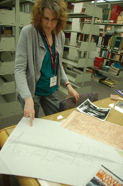 Shari Theroux, a librarian at the Beulah Williams Library on the campus of Northern State University, looks at some of the items Aberdeen resident George Nikolas gave to the library's collection.