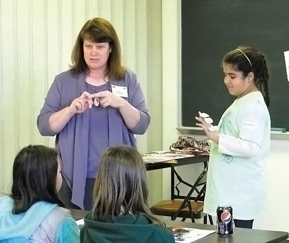 4-H Leader LeAnn Johnson, left, demonstrates the bone structure in humans and horses as bone labels are stuck on a willing volunteer at this year's 4-H Horsemanship Standards Learning Day.
