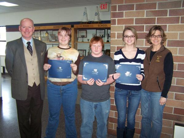 John M. Crinnion, Farm Bureau Insurance agent (from left), is shown with Pellston America & Me essay contest winners: first place Karissa Hardwicke, second place Jake Daily, third place Molly Crossley; and eighth-grade teacher/contest coordinator Wendy Laser.