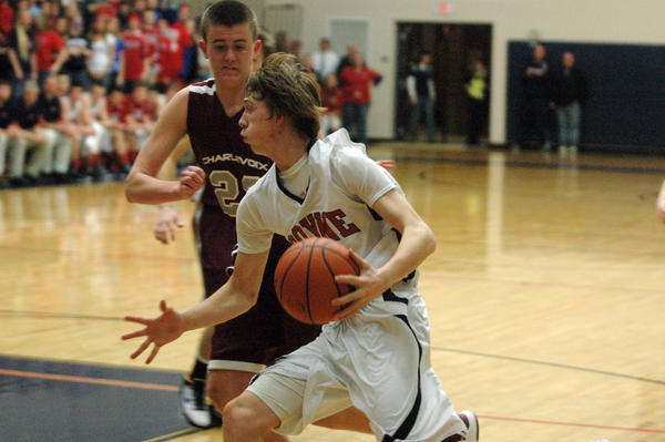 Boyne City junior forward Ryan Carson (right) looks to drive to the basket on Charlevoix senior Chandler Novotny during Monday's Class C district contest at the Boyne City High School gym. The Ramblers defeated the Rayders, 46-42.