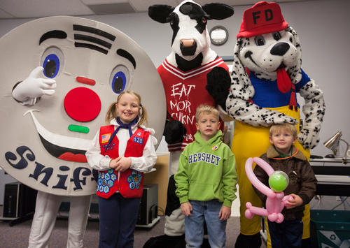 Front row from left, Madilyn Mago, 8, David Magno, 5, and Matthew Goldsmith, 3, all of Laurel, stand for a photo with mascots Sniffy the Smoke Detector, Chick-fil-a cow, and the Fire Dog.