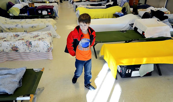 Drew Lobley, 6, walks past beds at the REACH cold weather shelter while taking a tour with his dad and shelter administrator Nancy Derrick on Monday afternoon. Drew collected blankets and pillows to donate to the shelter.