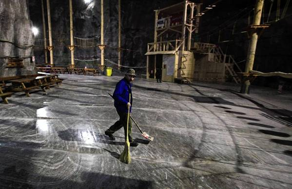 A worker wipes the salt floor inside Praid Salt Mine.