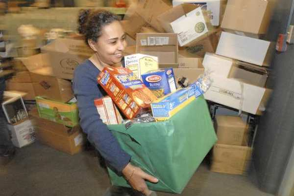 A volunteer carries a one of nearly 500 food boxes packed for needy families a Holiday Basket event four years ago.