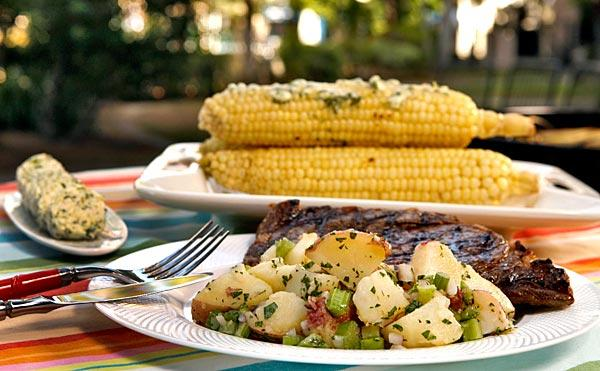 Steak, potato salad with celery and roasted corn.