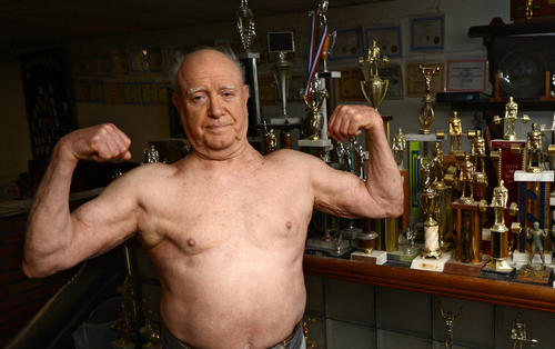 Fred Glass, 76, of Allentown poses next to the hundreds of trophies he's won in his basement gym. Glass is an international weight-lifting champion and can still lift more than 400 pounds.