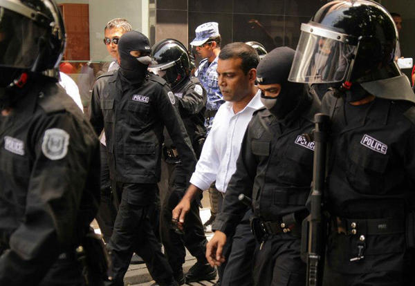 Former Maldivian President Mohamed Nasheed, center, is surrounded by police after his arrest in Male, capital of the Maldives.