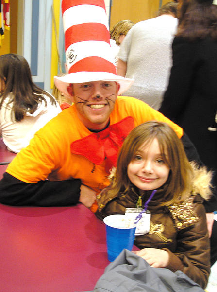 "Salem Avenue Elementary School teacher Chris Grove, who dressed as the Dr. Seuss character ""The Cat in the Hat,"" shares an ice cream float with third-grader Olivia Vandyke at the school's family reading night Feb. 27."