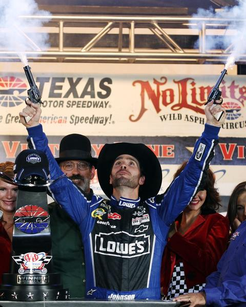 Jimmie Johnson fires blanks from a pair of revolvers as he celebrates his win in victory lane following the NASCAR Sprint Cup Series race at Texas Motor Speedway in Fort Worth in November.