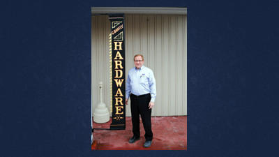 Rob Bantly, owner of Bantly Hardware, stands next to the 150-year-old sign that was purchased by his great-great-grandfather.