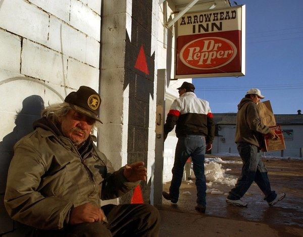 John Red Shirt sits outside one of the convenience stores that sell beer in Whiteclay, Neb., just across the state line from South Dakota's Pine Ridge Indian Reservation.