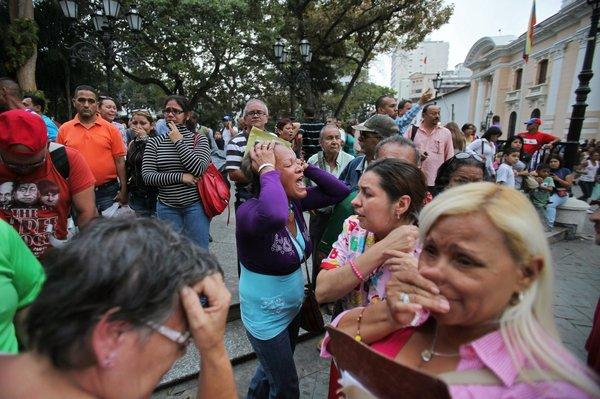 Supporters of Venezuelan President Hugo Chavez react after the vice president announced Chavez's death in downtown Caracas.